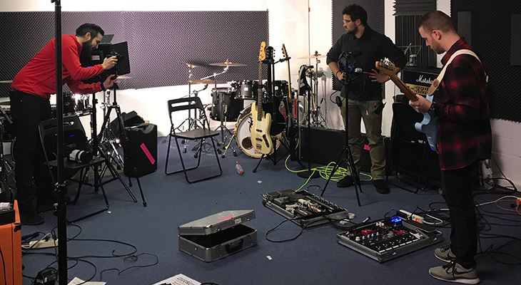 Cameras, light and filming people in the band room of invoker