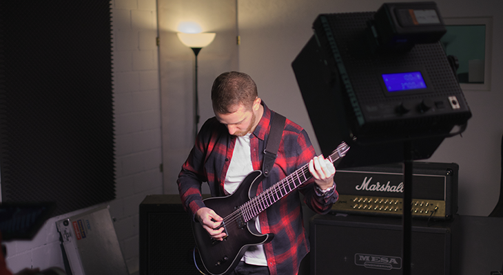 Andy with his black guitar in the spot light while grabing the video