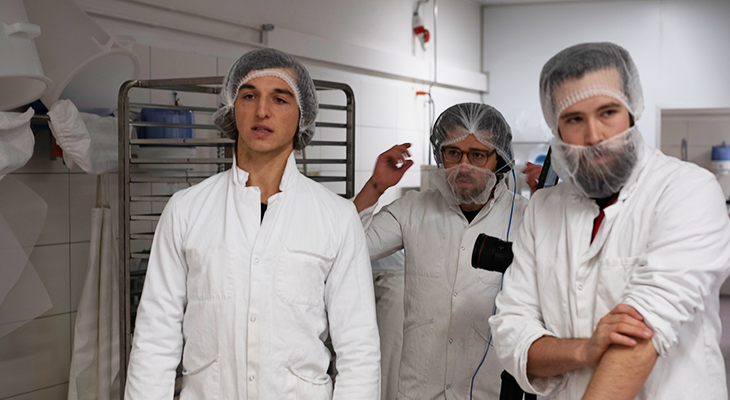 Movie production team with new roots founder Freddy Hunziker in the production area with hair net around the head and the beard.
