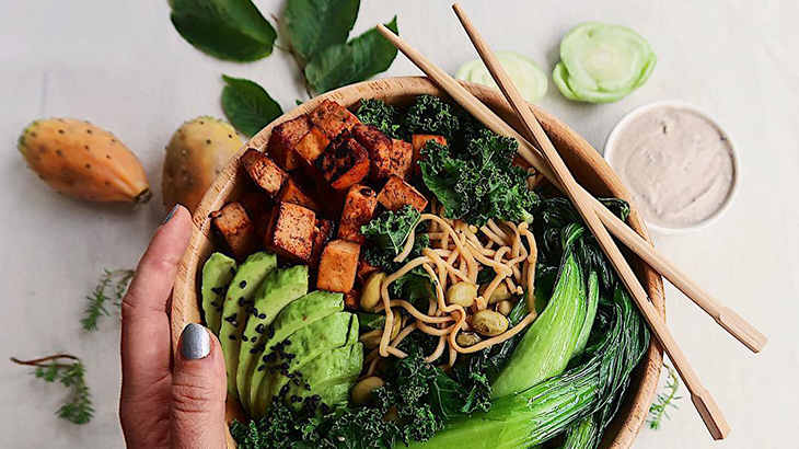 A dish from Carey Shoemaker with tofu and kale in a wooden bowl with wooden sticks.
