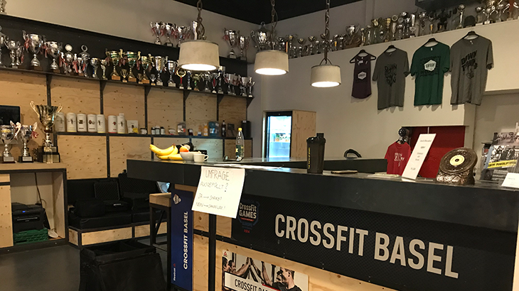 Four shelf units on two walls are full of golden and silver glittering trophys and cups in the training center of Crossfit Basel.