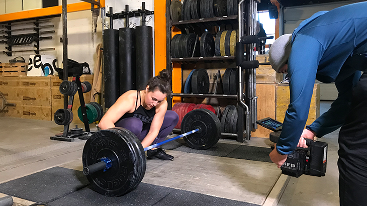 Nora Jäggi is preparing her barbell with weights on the wooden floor. The camera man on the rights side captures the situation.