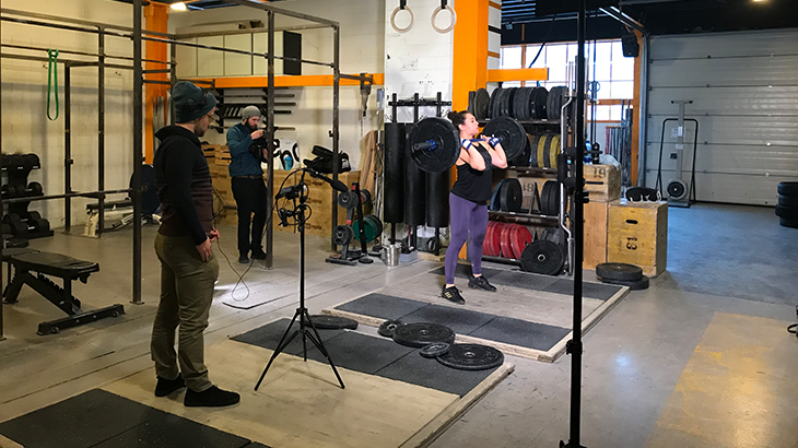 Nora Jaeggi lifts the weight while the filming team is grabing picture and sound from the side and from behind.