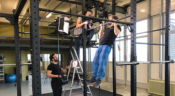 Matthias performing pull ups while the filming team is grabing him.