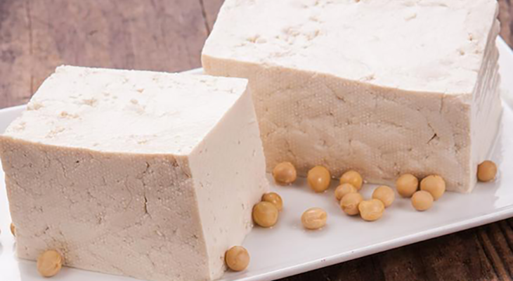 Tofu blocks on a plate and soy beans around
